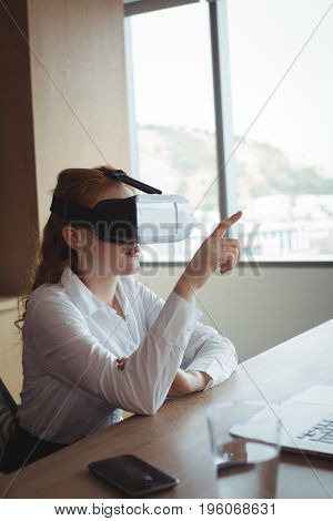 Businesswoman anticipating while using virtual reality technology at desk in office