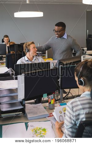 Male business colleagues dicussing at desk in office
