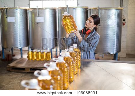 Female worker checking oil bottles in factory