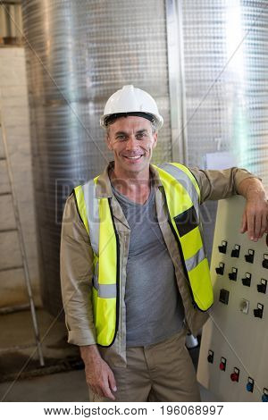 Portrait of happy technician standing near machine in oil factory