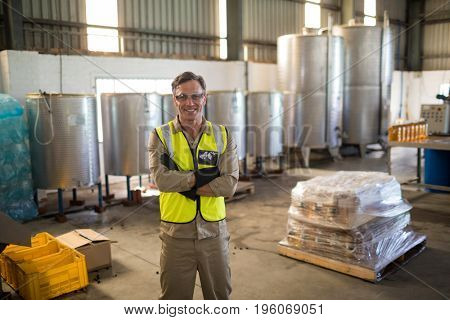 Portrait of happy technician standing with arms crossed in oil factory
