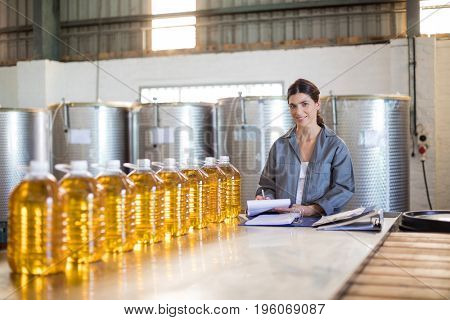 Portrait of female worker maintaining record in notepad at factory