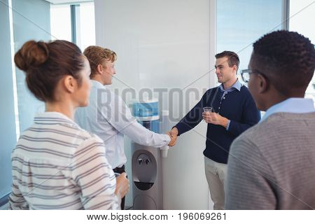 Young business colleagues shaking hands while holding drinking glass at office