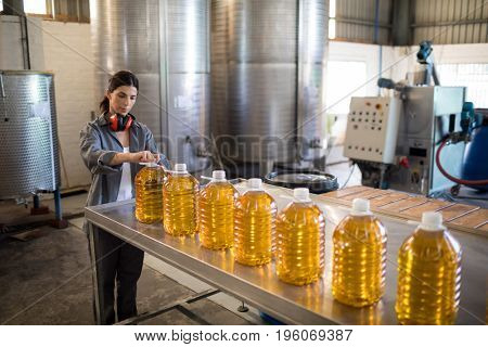 Attentive female worker working in oil factory