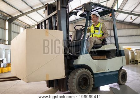 Worker carrying package with forklift in oil factory