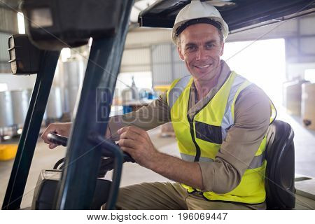 Portrait of happy worker driving forklift in oil factory