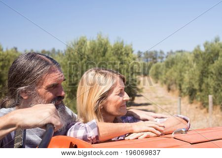 Thoughtful couple standing near tractor in olive farm on a sunny day