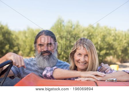Portrait of happy couple standing near tractor in olive farm