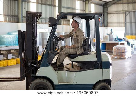 Worker driving forklift in oil factory