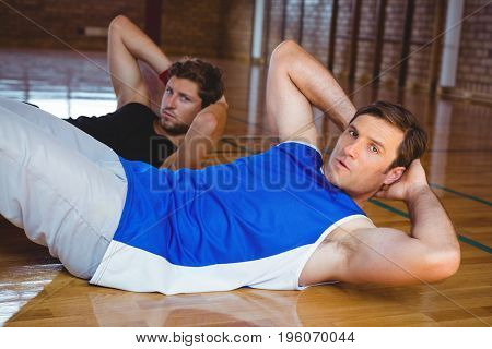 Male friends practicing side crunches in court
