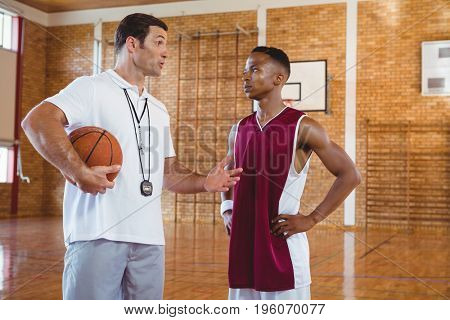 Coach guiding basketball player while standing in court