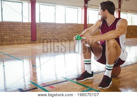 Male basketball player looking away while sitting on basketball in court