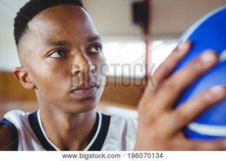 Close up of teenage boy practicing basketball in court