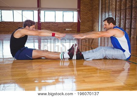 Side view of male friends exercising while sitting on floor in court
