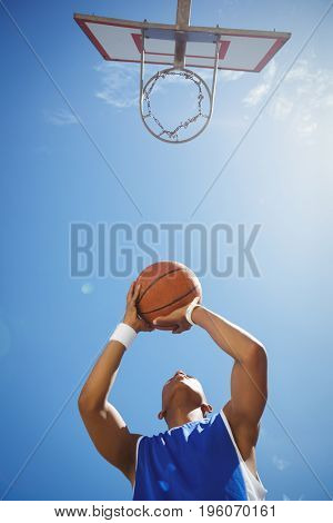Directly below shot of teenage boy playing basketball against sky on sunny day