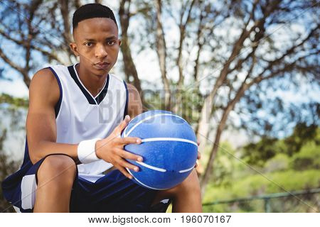 Portrait of male teenager with basketball sitting on bench in court