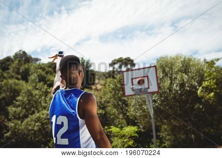 Rear view of male teenager practicing basketball in court on sunny day