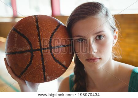 Close up portrait of female basketball player with ball in court