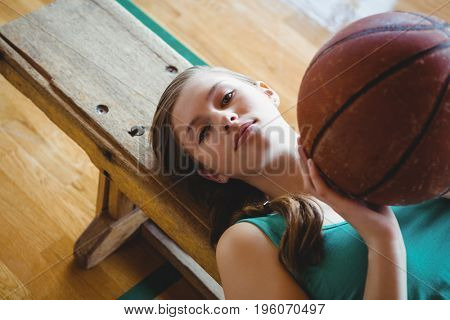 High angle portrait of woman with basketball lying on bench in court