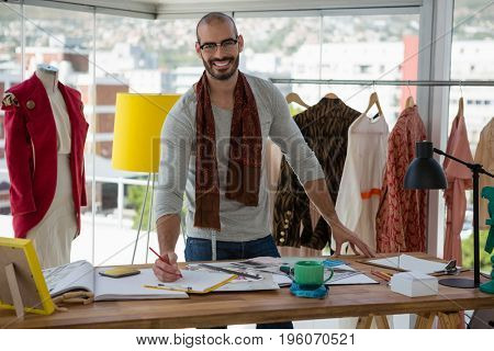 Portrait of smiling male designer drawing sketch at table in studio
