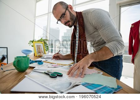 Male designer drawing sketch while standing in workshop