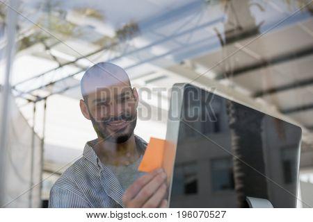 Smiling designer using computer in studio seen through glass