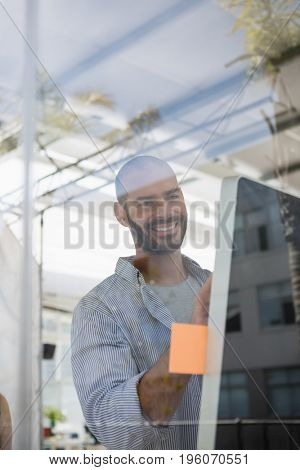 Smiling designer using computer while standing in studio seen through glass