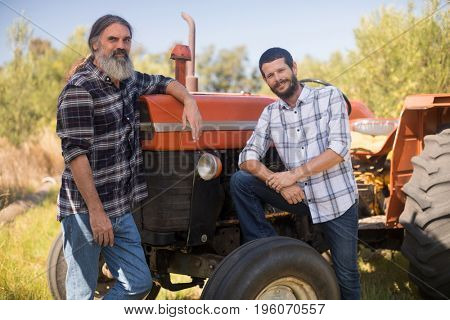 Portrait of confident friends standing near truck in olive farm