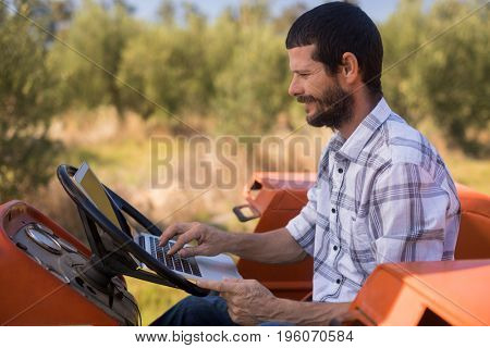 Man using laptop in tractor on a sunny day