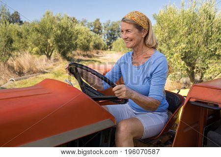 Happy woman sitting in tractor on a sunny day