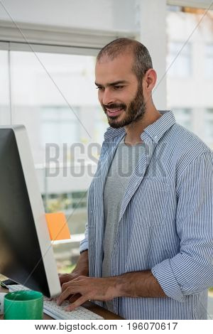 Smiling designer using computer while standing in studio