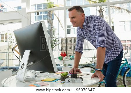 Smiling designer using computer while standing at desk in office