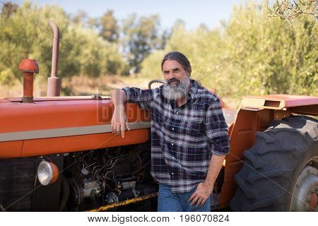 Portrait of confident man leaning on tractor in olive farm