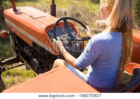 Rear view of woman driving tractor in olive farm on a sunny day