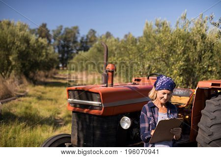 Woman leaning on tractor while writing on clipboard in olive farm