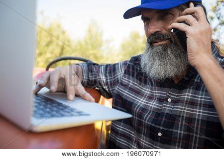 Man using laptop while talking on mobile phone in olive farm