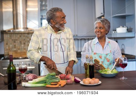 Smiling couple talking while preparing food in kitchen at home