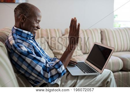 Side view of senior man video conferencing over laptop while sitting on sofa at home