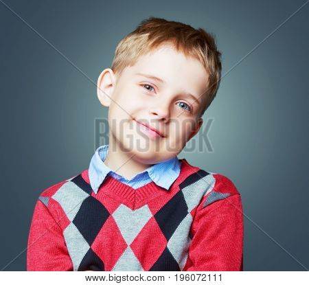 happy beautiful child wearing a sweater  isolated against grey background