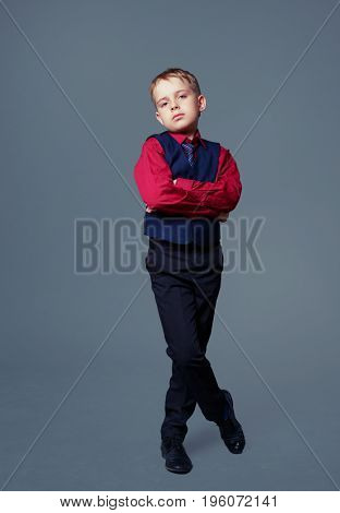 displeased child isolated against grey background