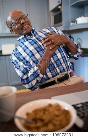 Senior man suffering from chest pain while sitting in kitchen