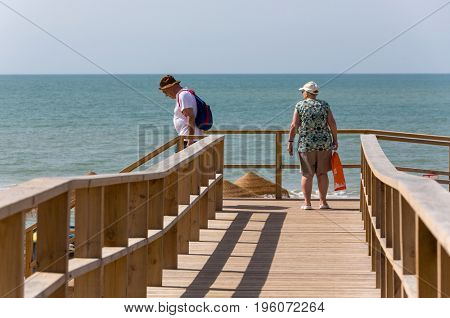 ALVOR, PORTUGAL - APRIL 23, 2017: Old couple at the famous beach of Praia do Alvor, Algarve region, Portugal