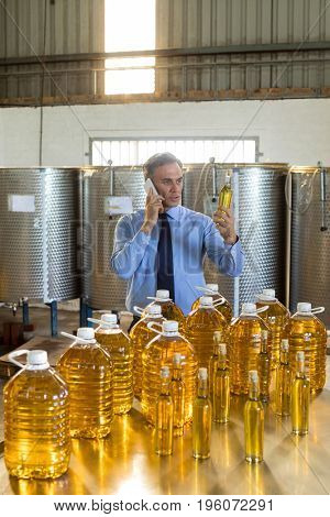 Manager talking on mobile phone while examining olive oil in factory