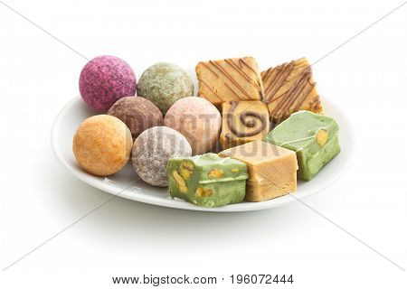 Various sweet candies on plate isolated on white background.