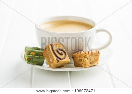 Colorful caramel candies and coffee cup on white table.