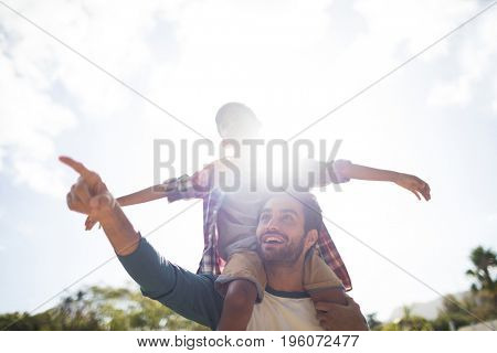 Happy father gesturing while carrying son on shoulder in yard against sky