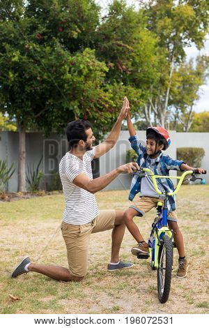 Full length of father and son doing high five while cycling in yard