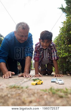 Boy and grandfather playing with toy cars while kneeling on pavement in yard against sky