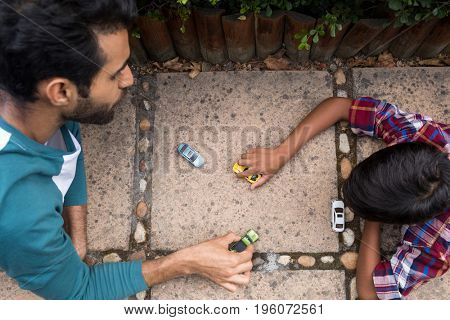High angle view of father and son playing with toy car in yard