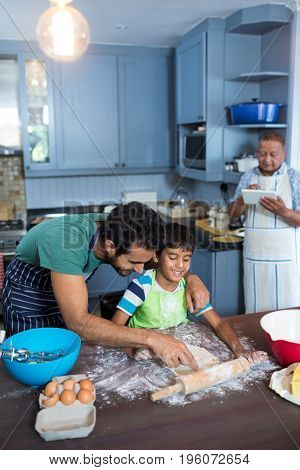Father assisting son for rolling dough with man using tablet in background